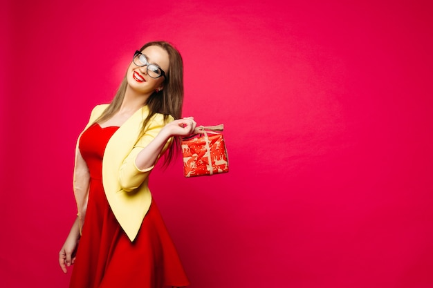 Positive girl holding present box over shoulder.