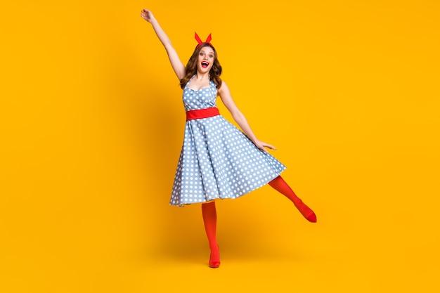 점선 드레스에 긍정적 인 소녀는 노란색 배경에 잡는 것처럼 손을 잡으십시오