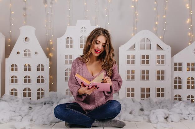 Позитивная девушка в вязаном фиолетовом свитере сидит на полу и переворачивает страницу книги. портрет молодой кудрявой женщины с красной помадой, читающей против стены игрушечных домиков и гирлянд.