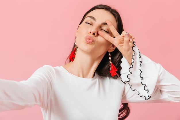 Позитивная девушка в белой блузке делает селфи и показывает знак мира на розовом фоне.