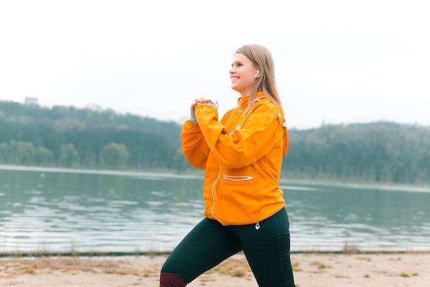 ポジティブな女の子は、イヤポッドで音楽を聴きながら、湖の近くの公園で朝のエクササイズをしています。
