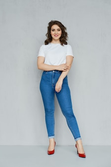 Positive girl in jeans, white t-shirt and red stilettos posing
