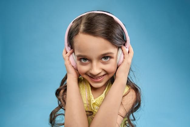 ヘッドフォンでお気に入りの曲を聴く肯定的な女の子