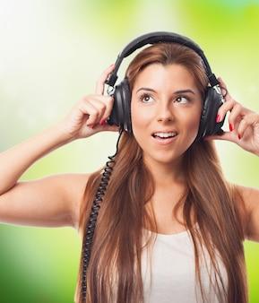 Ragazza positiva ascoltando musica in cuffia.