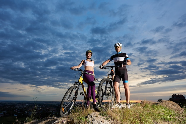 Positive girl and man posing with bikes in helmets and sportswear.