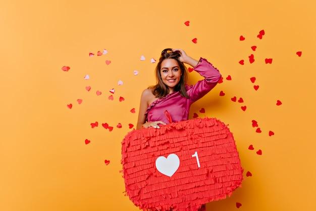 Позитивная девушка позирует с интернет-баннером. радостная брюнетка женщина, стоящая на желтом с красным конфетти.