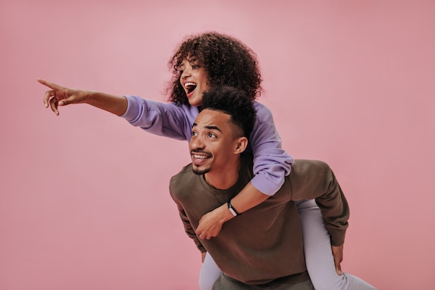 Positive girl in purple outfit sitting on her boyfriends back and pointing to left