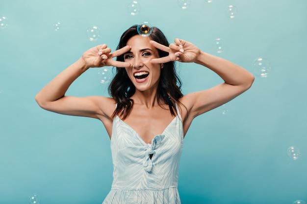 Позитивная девушка показывает знак мира на синем фоне с мыльными пузырями