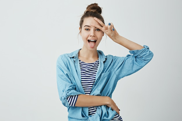 Positive girl shows her emotions. indoor shot of attractive slender caucasian female student sticking out tongue and showing v sign over forehead, being in good mood