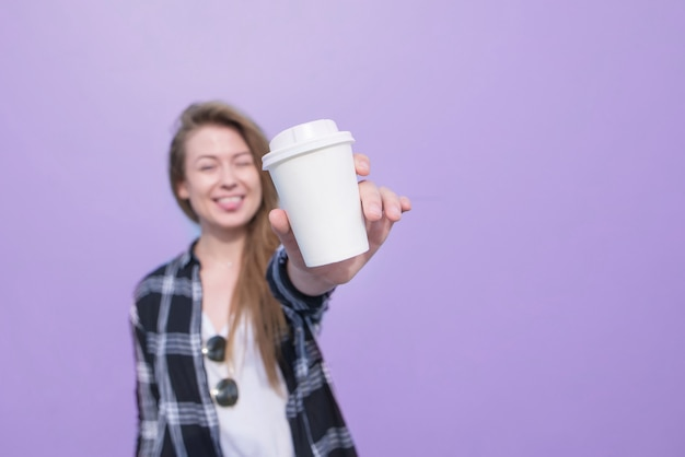 Positive girl shows a white glass with coffee on a purple background.