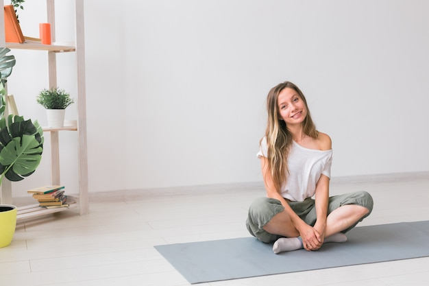 필라테스 또는 요가 연습 후 휴식을 취하는 피트니스 매트에 앉아 있는 긍정적인 소녀와 마음챙김