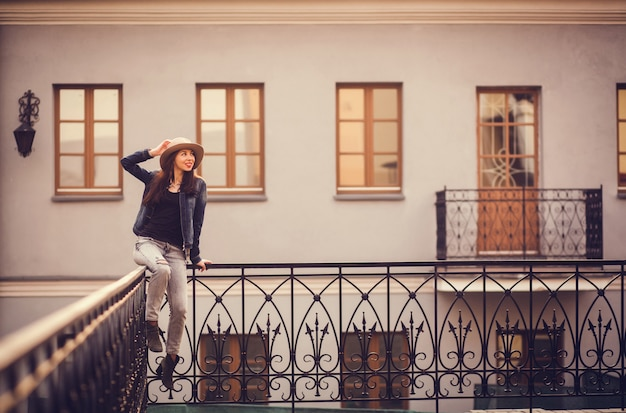 Positive girl sitting on the railing near the building