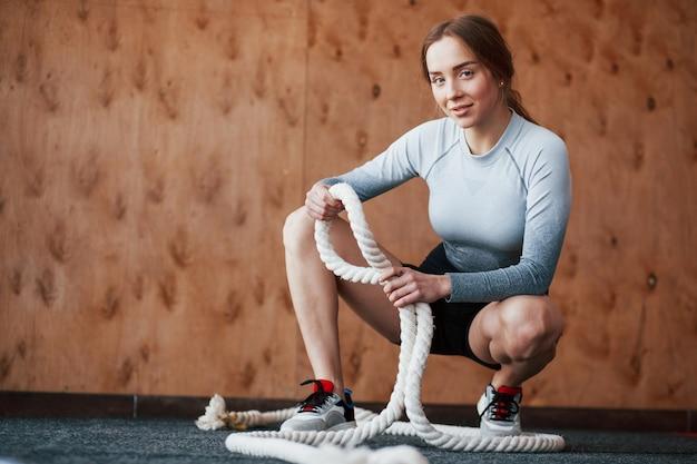 Положительная девушка. спортивная молодая женщина имеет фитнес-день в тренажерном зале в утреннее время