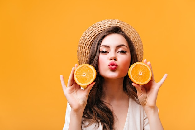 La ragazza positiva in cappello di paglia soffia il bacio, esamina la macchina fotografica e tiene metà dell'arancia.