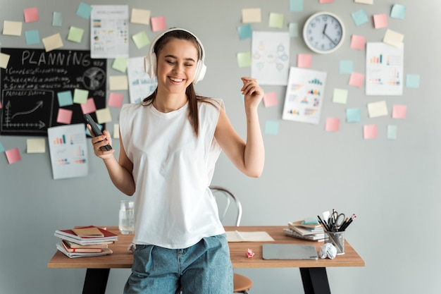 헤드폰에 긍정적 인 여자 학생은 컬러 스티커와 함께 회색 배경에 바탕 화면 근처의 그의 방에 서 있습니다.
