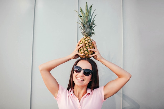 Positive girl in sunglasses stands and holds pineapple on her head. she keeps it in balance with hands.