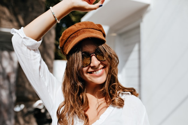 Positive girl in sunglasses and velvet cap raised her hand and smiling against buildings.