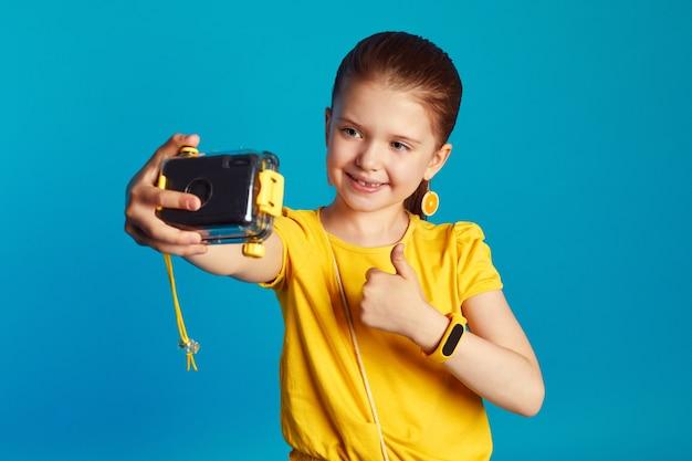 Позитивная девушка делает селфи с камерой, широко улыбается жестом мира