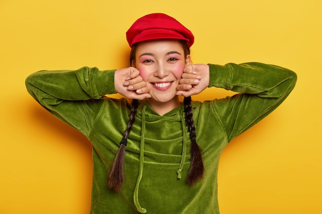 긍정적 인 소녀는 뺨을 만지고, 손을 옆으로 유지하고, 즐겁게 미소를 짓고, 빨간 베레모와 녹색 벨벳 스웨트 셔츠를 입습니다.