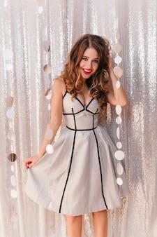 Ragazza positiva con capelli ricci in vestito festivo alla moda che propone alla festa sulla parete splendente luminosa.