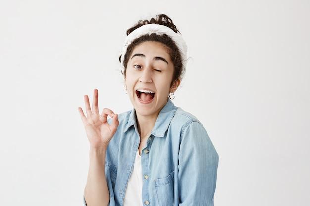 Положительная девушка с темными волосами в рубашке джинсовой ткани плюшки нося и do-rag, моргая и раскрывая рте при радость показывая одобренный знак будучи радостным после встречи с его парнем изолированным против белой стены.