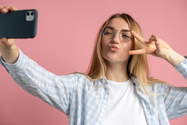 眼鏡をかけたポジティブな女の子はピンクの背景に自分撮り