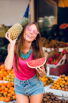 Positive girl with a great smile holding ananas and slice of watermelon on market
