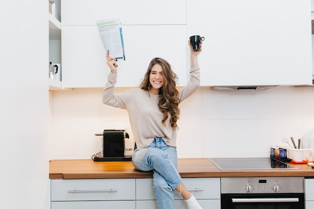 Positive girl with long dark hair holding magazine and cup of tea