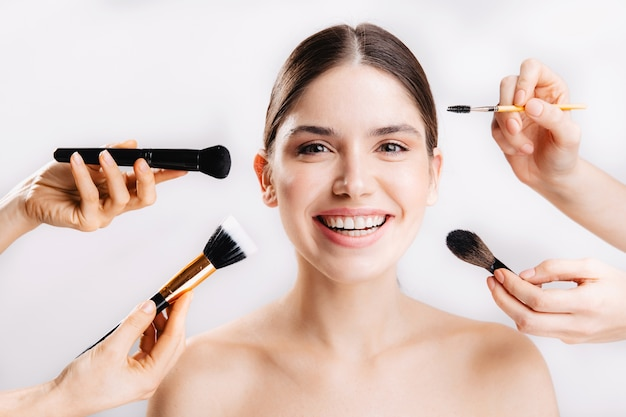 Positive girl with perfect skin is smiling, while many hands with brushes reaching for her face on isolated wall .