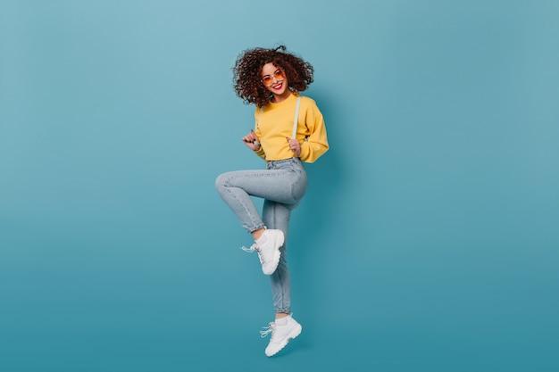 Ragazza positiva con rossetto rosso vestita in felpa gialla e pantaloni skinny in denim che salta sullo spazio blu. istantanea della signora riccia con gli occhiali arancioni.