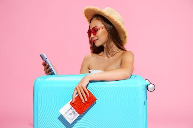 Позитивная девушка с чемоданом, билетом и паспортом собирается путешествовать, бронируя отель по телефону
