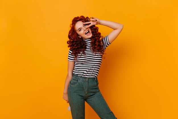 롤리팝을 들고 감정적으로 카메라를보고, 평화 기호를 보여주는 물결 모양의 빨간 머리를 가진 긍정적 인 소녀.