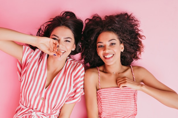 Positive girlfriends lying down enjoying rest in pink girl's room. portrait of tanned brunettes in striped sundresses.