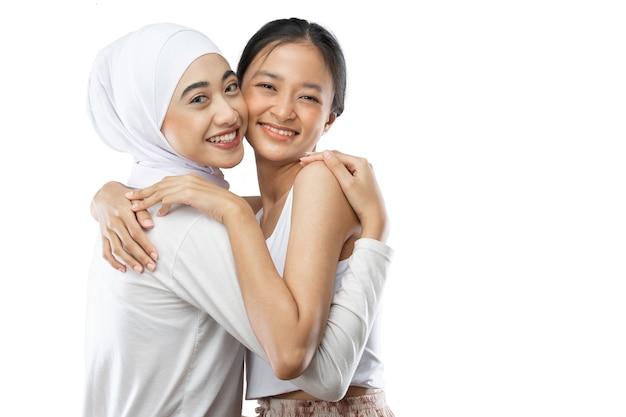 さまざまな宗教のポジティブな女の子が、友好的な関係で心地よい笑顔を並べて立っています...