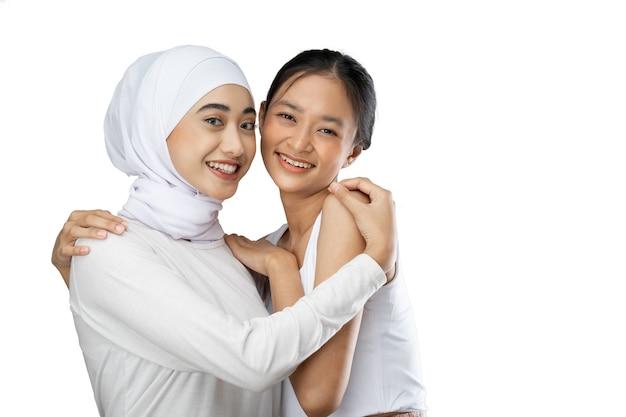 お互いに抱き合って友好関係の隣に立っている異なる宗教のポジティブな女の子