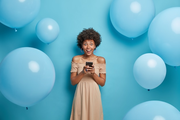 Positive glad african american woman holds mobile phone in hands and happy to chat with friends in social networks, wears cocktail dress, poses against blue wall in decorated photo zone