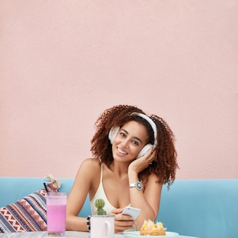 Positive glad dark skinned african american woman dressed casually, being lover of music, listens songs from playlist, surrounded with fresh cocktail