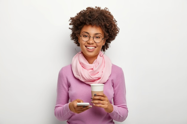 Positive good looking adult woman with curly hair, wears optical glasses, violet clothes, uses smartphone device to upload something from internet, drinks aromatic hot beverage from paper cup