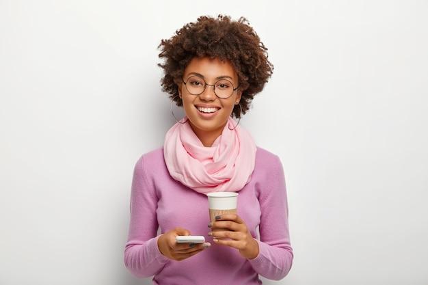 Positiva bella donna adulta con i capelli ricci, indossa occhiali da vista, vestiti viola, utilizza il dispositivo smartphone per caricare qualcosa da internet, beve bevanda calda aromatica dal bicchiere di carta