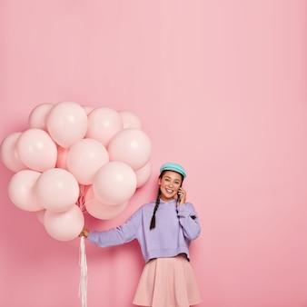 긍정적 인 잘 생긴 생일 소녀는 휴대 전화를 통해 의사 소통을 즐기고, 파티 속성을 전달하고, 세련된 옷을 입고, 좋은 소식을 공유하고, 화장을하고, 뺨이 붉고, 실내에서 재미를 느낍니다.