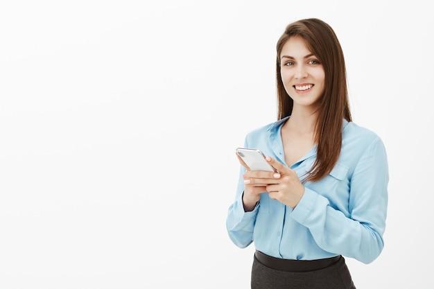 Positive good-looking brunette businesswoman posing in the studio