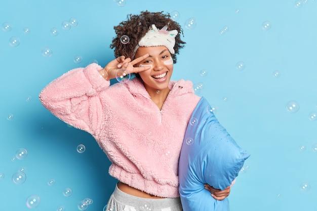 Позитивная симпатичная кудрявая женщина делает жест победы над широко улыбающимся лицом