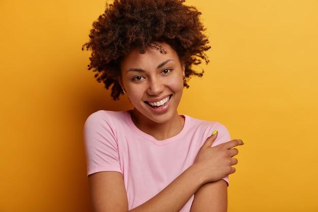 巻き毛のポジティブな格好良い巻き毛の女性は、心地よく笑顔で、良い感情を表現し、魅力的な外観を持ち、カジュアルな服を着て、黄色の壁の上でポーズをとります。幸福の概念