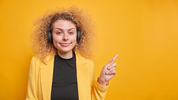 Позитивная симпатичная кудрявая молодая женщина в строгой одежде указывает на пустое место, дает рекомендацию, предлагает разместить здесь вашу рекламу, использует беспроводные наушники позы в помещении
