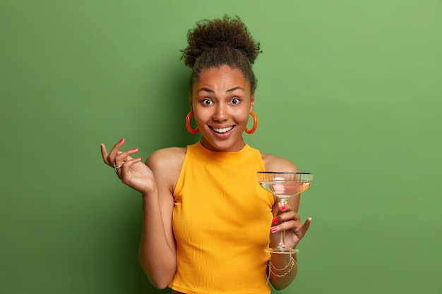 Positive good looking ethnic female poses with glass of summer cocktail, has happy look and nice talk with friend, wears yellow clothes isolated on green wall. people, drinking, leisure concept
