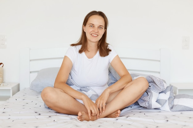 Positive good looking female wearing white casual t shirt sitting in light bedroom on bed, looking at camera with pleasant smile, expressing happiness.