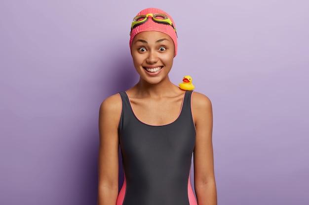 건강하고 어두운 피부를 가진 긍정적 인 잘 생긴 여성, 광범위하게 미소