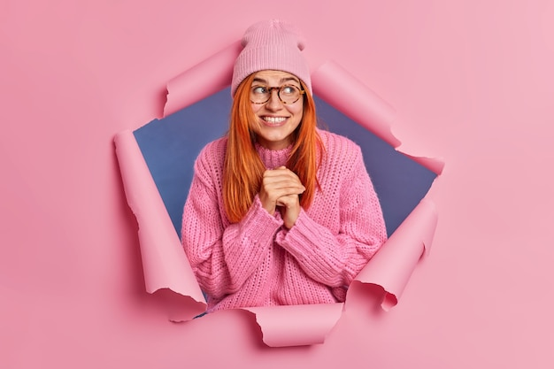 La giovane donna positiva allo zenzero di bell'aspetto tiene le mani unite sorride ampiamente e distoglie lo sguardo attende che accada qualcosa di buono indossa occhiali da cappello maglione invernale.