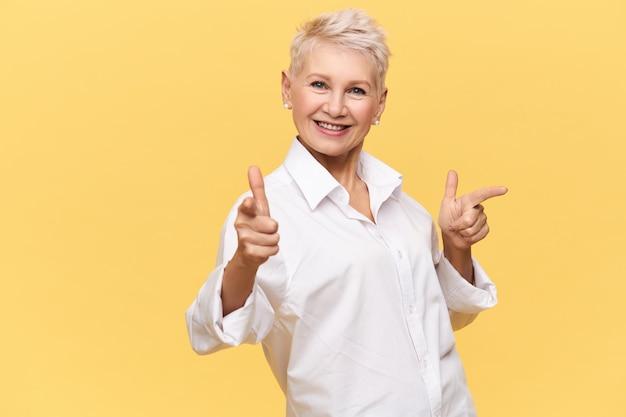 ピクシーの髪型のポーズでポジティブな格好良い中年のヨーロッパの女性。人差し指、広告商品を指す白いシャツのうれしそうな女性。本物の人間の感情