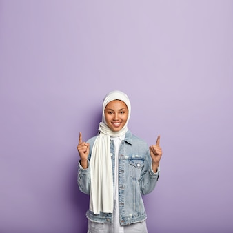 La bella signora musulmana positiva punta in cima, reagisce su un fantastico spazio di copia promozionale